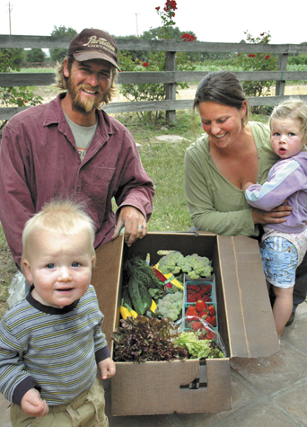 Parents Christopher and Johanna with daughter, Ashlin, and son, Quinton, and a box of fresh CSA subscriber organic produce. CSA customers come to the farm weekly to pick up a box of the week's produce.