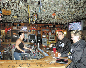 From Left, bartender Valerie Lesher shares a laugh with tourists Oscar Alcaraz and Krista Vernon at the maverick. Many visitors to the Maverick write notes on a dollar bill and affix it to the ceiling.