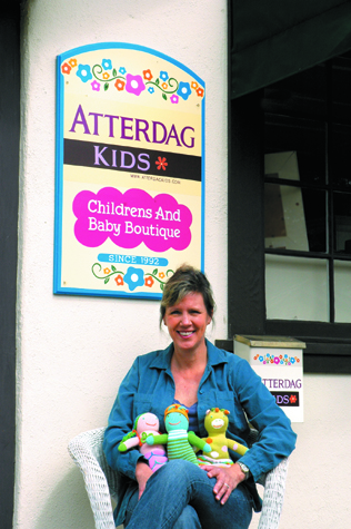 On the porch of the bungalow that houses her thriving children's and baby boutique, owner Laura Healey is holding handmade Bla Bla dolls.