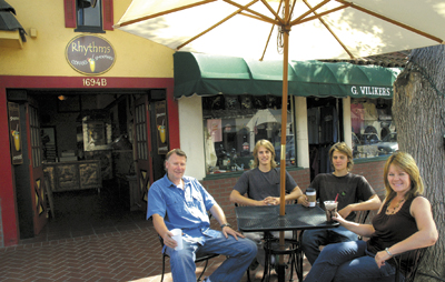 Enjoying an afternoon coffee drink under the sidewalk umbrella at their family-owned Rhythms Coffee & Smoothies business on Copenhagen Drive are, from left, sons David, Mickey and Stefan, and Caroline Esdaile. Missing from the family photo is the Esdailes'  daughter, Haley, who was attending a school event.