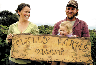 Johanna, Christopher and their daughter Ashlin with the handmade sign for their successful family-owned farm.